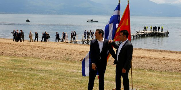 Macedonian Prime Minister Zoran Zaev (R) and Greek Prime Minister Alexis Tsipras react after the signing...