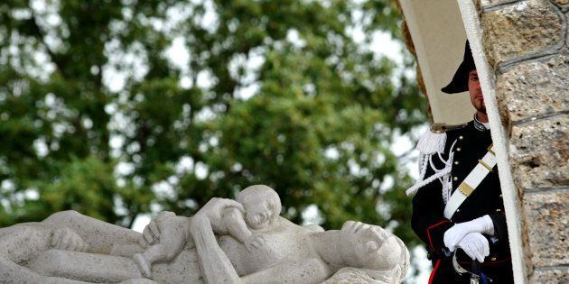 An Italian Carabiniere peers from a monument commemorating victims of a Nazi massacre as German Interior...