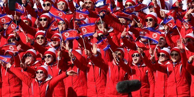 North Korean cheerleaders wave their flag as they watch their national skier compete in the Women's Slalom...