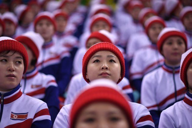 North Korean cheerleaders watch the men's preliminary round ice hockey match between South Korea and...
