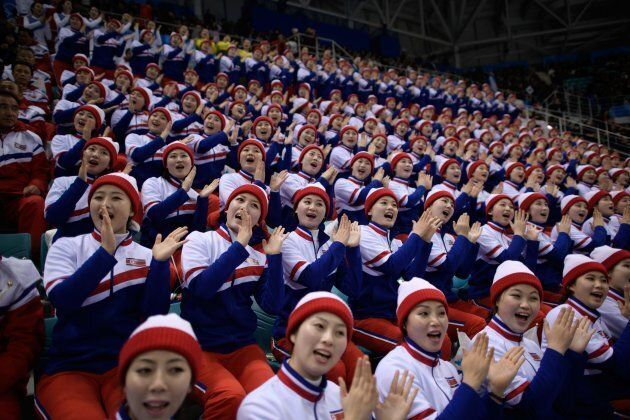 North Korean cheerleaders perform during the men's preliminary round ice hockey match between South Korea...