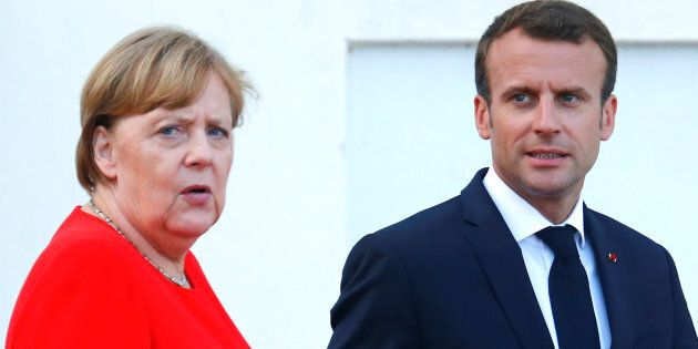 German Chancellor Angela Merkel and French President Emmanuel Macron react as they await European Commission...