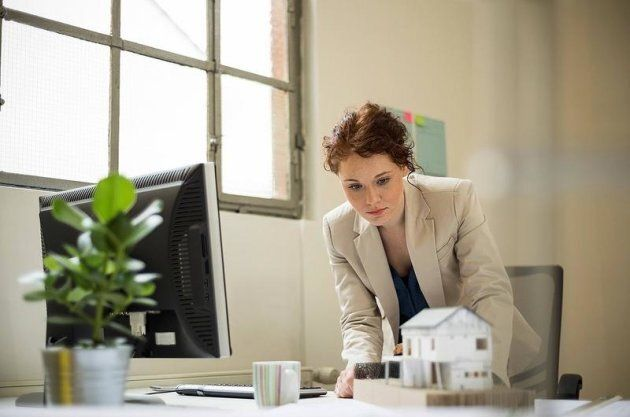 Young woman in office looking at architectural