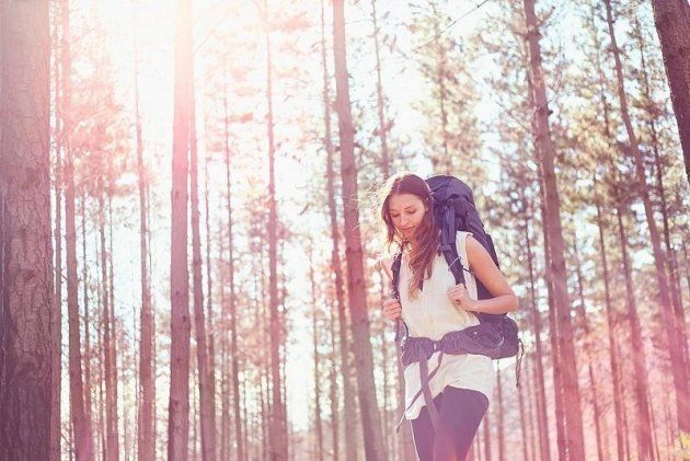 Young woman with backpack hiking in sunny