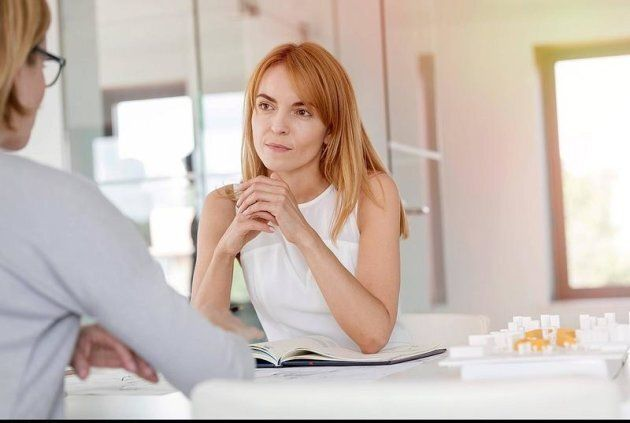 Attentive businesswoman listening to colleague in