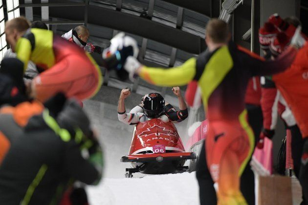 Canada's Alexander Kopacz and Justin Kripps celebrate as they slow down at the end of the in the 2-man...