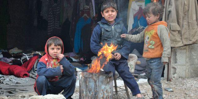 Tre bambini molto piccoli cercano di scaldarsi tra le macerie, a Ghouta Esta. In
