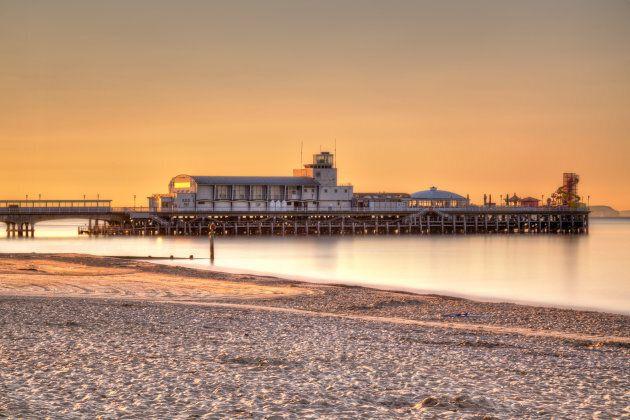 Tramonto sul Bournemouth Beach con il molo sullo sfondo. La spiaggia di sabbia bianca è una rarità nel...
