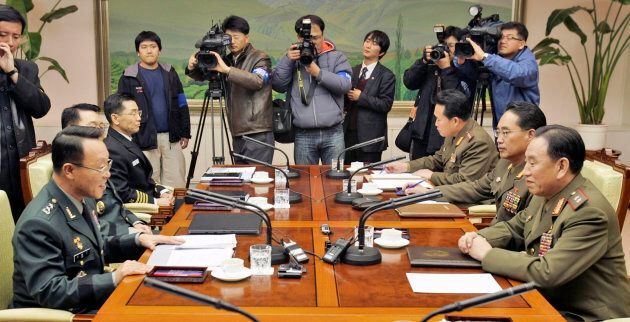 South Korea's chief delegate Lee Hong-kee (L) talks with his North Korean counterpart Kim Yong Chol (R)...