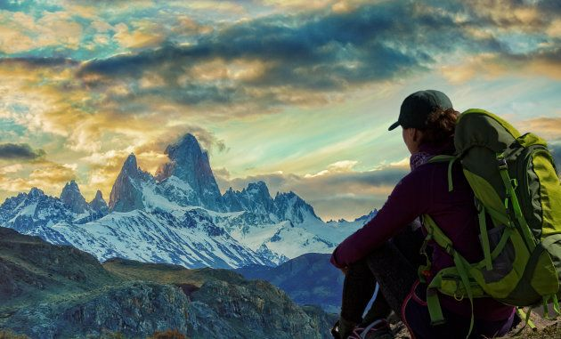 Female hiker rests and watches dramatic sky over Mount