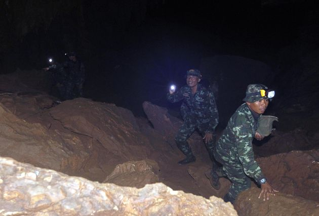 epa06840442 Thai military personnel search a cave during a rescue operation for missing football players...