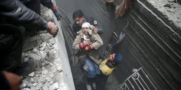 Syria Civil Defence members help an unconscious woman from a shelter in the besieged town of Douma, Eastern...