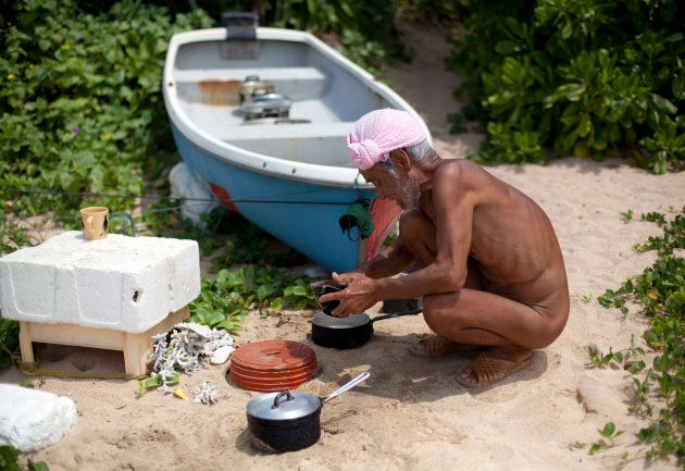 Seventy-six-year-old naked hermit Masafumi Nagasaki washes untensils on the beach on Sotobanari island,...