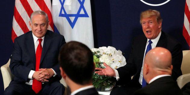 U.S. President Donald Trump speaks with Israeli Prime Minister Benjamin Netanyahu during the World Economic...