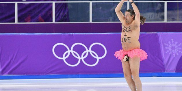 A shirtless man clad in a tutu dances on the rink following the men's 1,000m speed skating event medal...