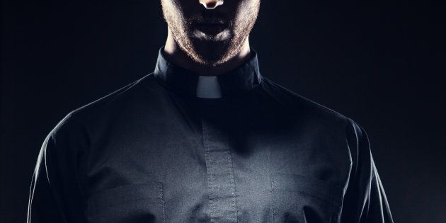 A dark high contrast image of a clergy man in a clerical collar holding a brown leather bound Bible in...