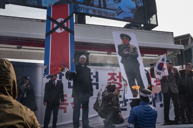 Anti-North Korean protests burn a North Korean flag during a rally against an upcoming visit by Kim Yong...