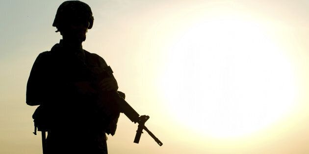 Silhouette of US soldier with rifle against a
