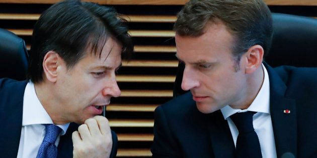Italian Prime Minister Giuseppe Conte talks with French President Emmanuel Macron during an emergency...