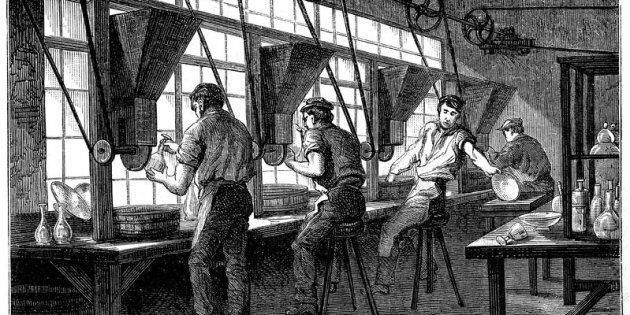 Glass cutters at their wheels, c1870. The vessel to be cut is held against a rotating wheel powered by...