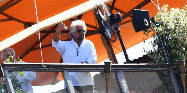 TOPSHOT - Five Star Mouvement (M5S) founder Beppe Grillo shows a silver bell from a hotel's roof garden...
