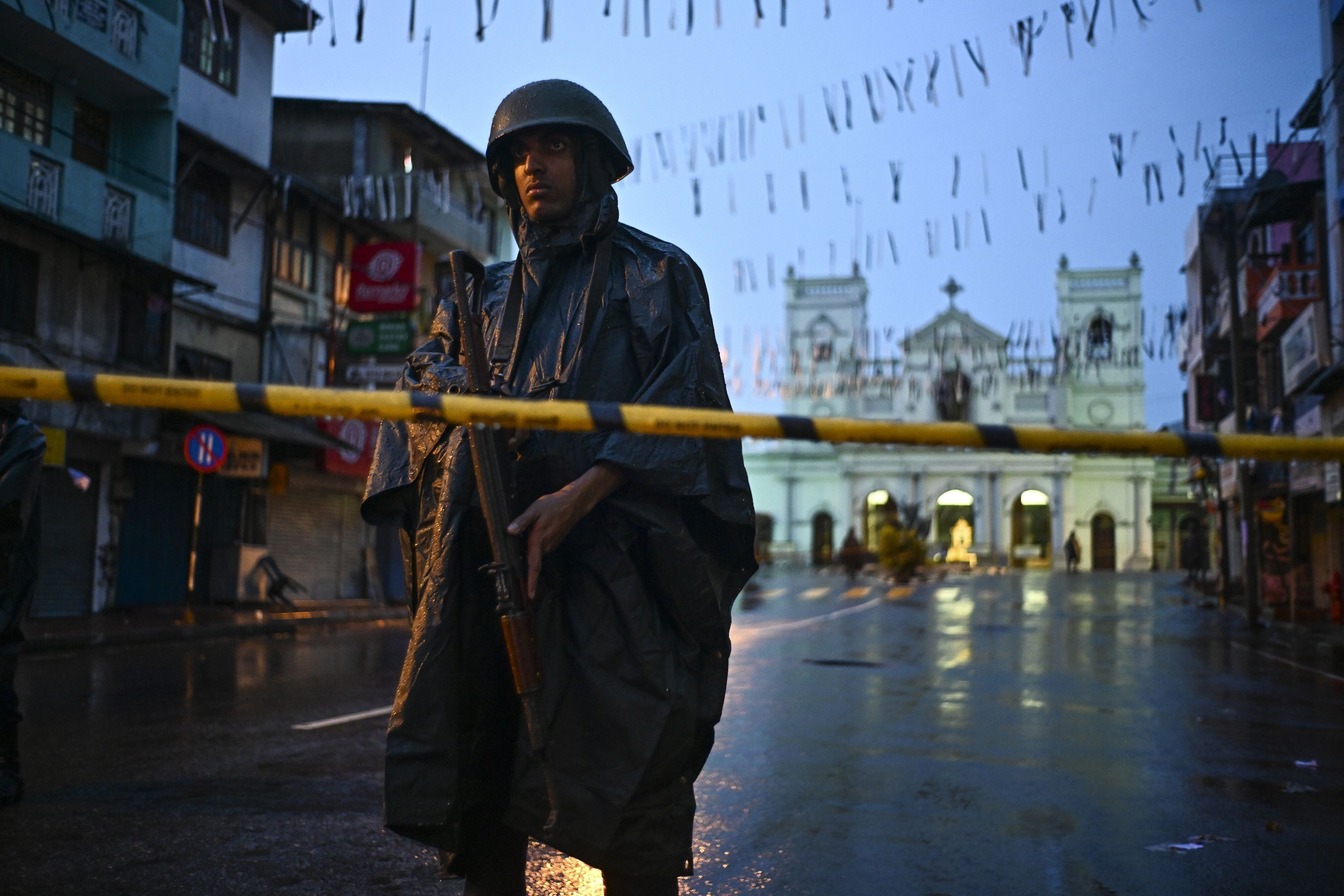 A Sri Lankan soldier stands guard under the rain at St. Anthony's Shrine in Colombo on April 25, 2019, following a series of bomb blasts targeting churches and luxury hotels on the Easter Sunday in Sri Lanka. - Sri Lanka's Catholic church suspended all public services over security fears on April 25, as thousands of troops joined the hunt for suspects in deadly Easter bombings that killed nearly 360 people. (Photo by Jewel SAMAD / AFP)        (Photo credit should read JEWEL SAMAD/AFP/Getty Images)