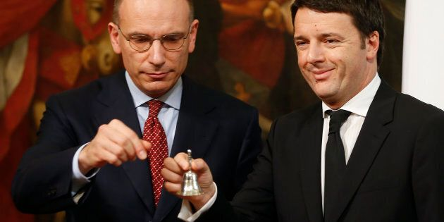 Newly appointed Italian Prime Minister Matteo Renzi (R) rings a silver bell to signify the start of his...