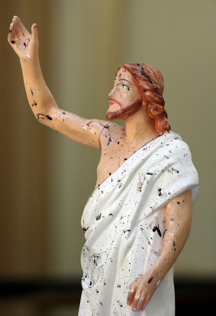 Blood stains are seen on a statue of Jesus Christ at St. Sebastian Catholic Church, after bomb blasts ripped through churches