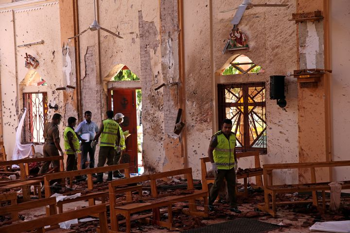 Police officers work at the scene at St. Sebastian Catholic Church, after bomb blasts ripped through churches and luxury hote