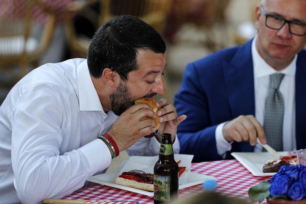 Matteo Salvini, ministro dell'Interno, al tavolo mentre mangia un panino con l'hamburger durante il ricevimento...