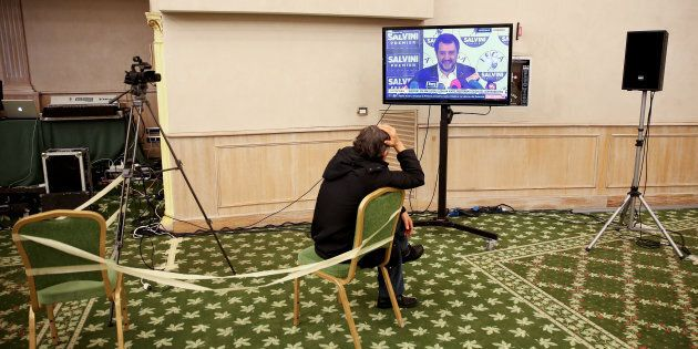 A man watches a screen showing Northern League party leader Matteo Salvini ahead of the start of a news...
