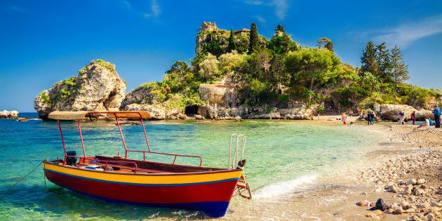 small boat for excursion in front of the island Isola Bella at Taormina,