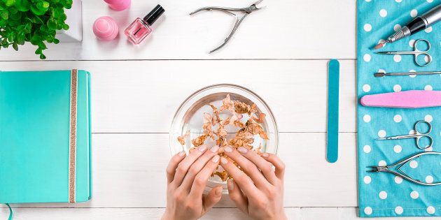 Beautiful woman's hands with perfect manicure in bowl of water on wooden background. Top view. Copy space....