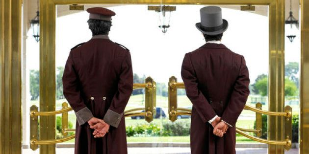 Concierge and bellboy standing at hotel entrance, rear