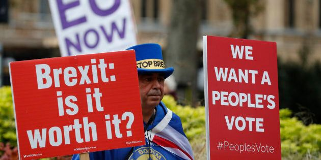 Pro and anti Brexit protesters hold placards as they vie for media attention near Parliament in London,...