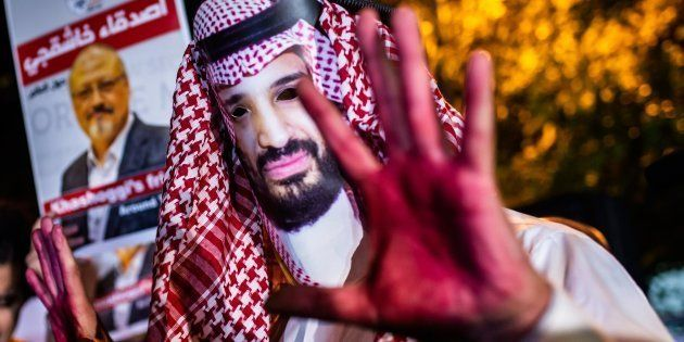 A protestor wears a mask of depicting Saudi Crown Prince Mohammad Bin Salman with red painted hands next...