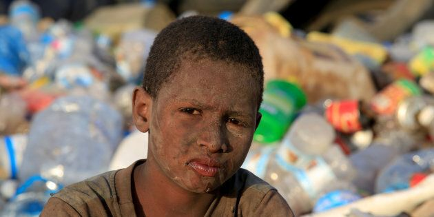 Ayoub Mohammed Ruzaiq, 11, poses for a photograph at a garbage dump where he collects recyclables and...