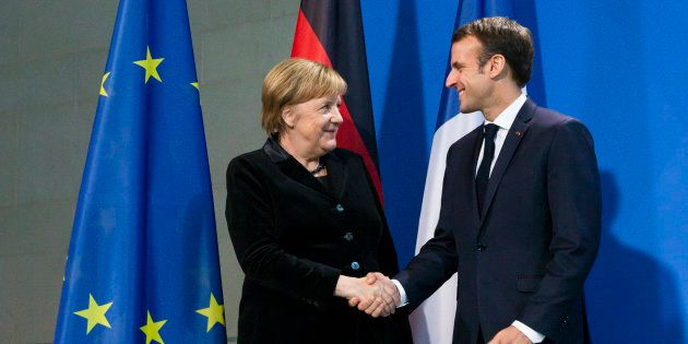 German Chancellor Angela Merkel and French President Emmanuel Macron shake hands after giving a statement...