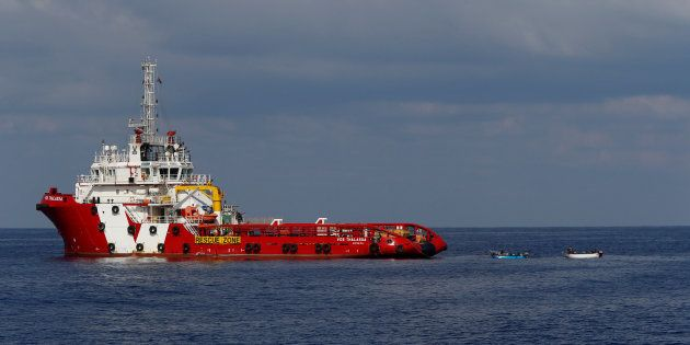 Wooden boats with migrants on board are seen tied to the offshore supply ship Vos Thalassa south of the...