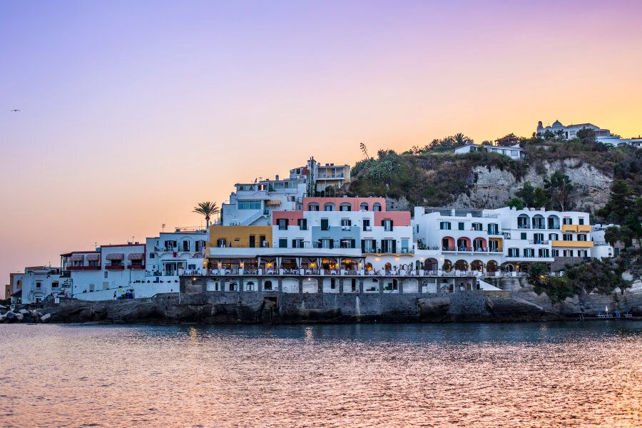 Pastel colored buildings by the shore at Island of Ischia, Campania, Italy. Photographed from a boat...