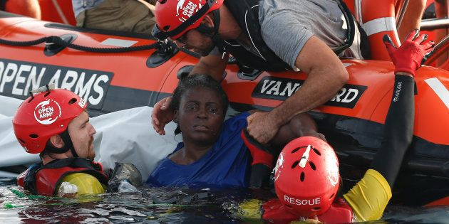 TOPSHOT - Members of the Spanish NGO Proactiva Open Arms rescue a woman in the Mediterranean open sea...