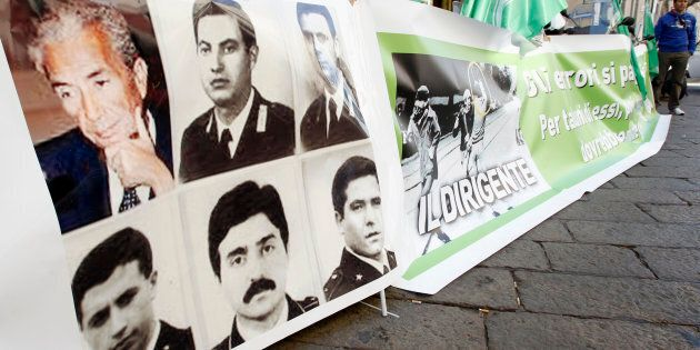 A banner with pictures of the 39th prime minister of Italy Aldo Moro (top L), and members of his escort...