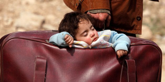 A child sleeps in a bag in the village of Beit Sawa, eastern Ghouta, Syria March 15, 2018. REUTERS/Omar
