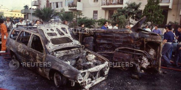 Burned cars are seen after a bomb attack that killed judge Paolo Borsellino and his police guards in...