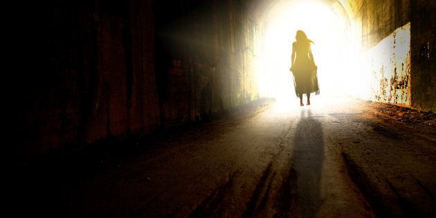 The figure of a woman in a dress floating to the light at the end of a