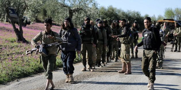 Turkish-backed Free Syrian Army fighters walk together after advancing north of Afrin, Syria March 17,...