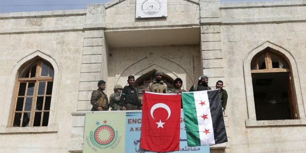 Members of Turkish forces and Free Syrian Army pose with their flags as they are deployed in Afrin, Syria...