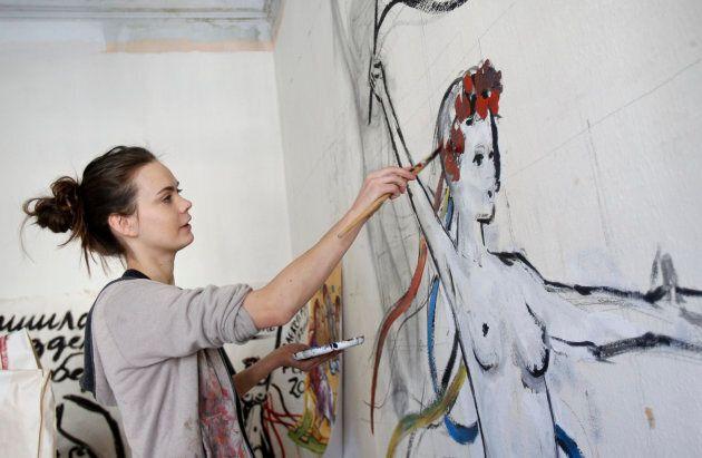 Femen activist Oksana Shachko paints a wall of her room in Kiev, February 21, 2012. Oksana, 25, one of...