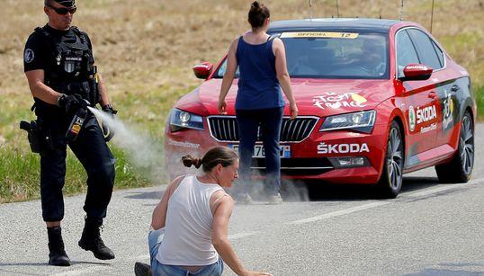 La manifestante è a terra, il poliziotto la colpisce con lo spray