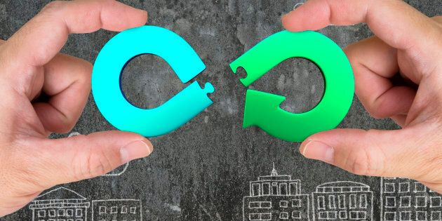 Circular economy concept. Two hands assembling arrow infinity recycling symbol of jigsaw puzzle pieces,...